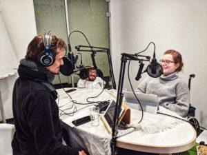 drei Menschen sitze um mikrofone herum