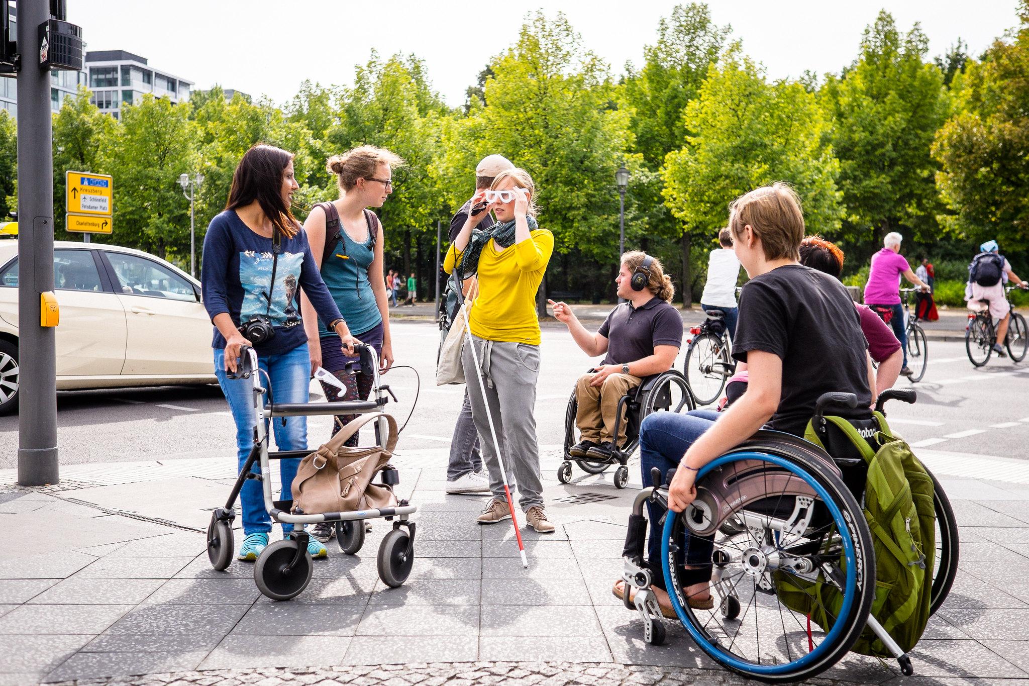 Eine Gruppe von Menschen sitz im Rollstuhl und andere stehen daneben. Sie tragen sommerliche Klamotten und reden miteinander.