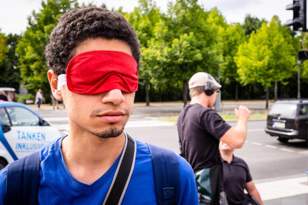 Ein Mann mit dunkelbraunen kurzen lockigen Haaren trägt einerote Schlafbrille. Im Hintergrund steht ein Mann der schwarze große Kopfhörer trägt.