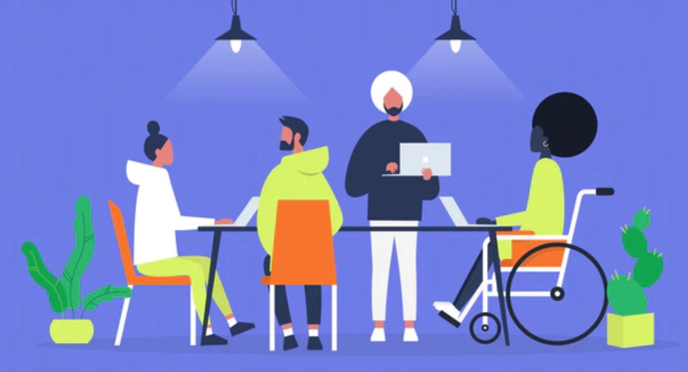 eine gruppe von menschen sitzt am tisch mit laptops, eine person sitzt in einem rollstuhl