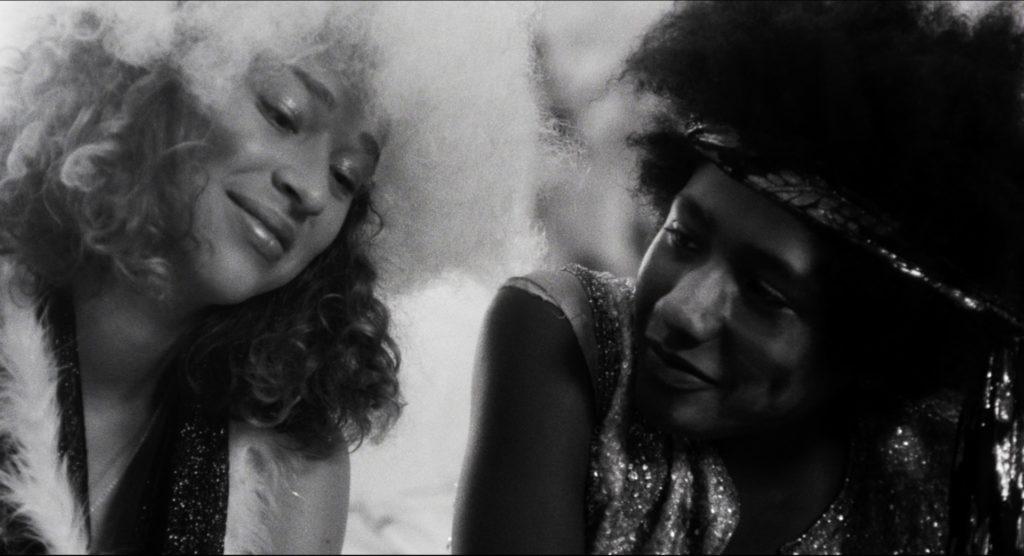 Ein schwarz-weiß bild von einer jungen Frau mit lockigen Haaren. Sie hat die Augen geschlossen. Das bild ist durch Rauch unscharf.
