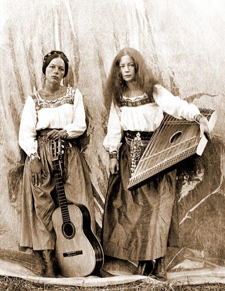 Ein schwarz-weiß Foto von zwei Frauen mit langen Haaren. Sie stehen nebeneinander und halten eine Gitarre und eine Zither in der Hand.