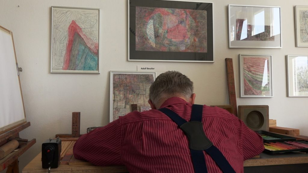 Ein älterer Mann mit rotem Hemd und schwarzen Hosenträgern sitzt an einem Schreibtisch. Er ist von hinten zu sehen. An der Wand hängen mehrere Bilder.