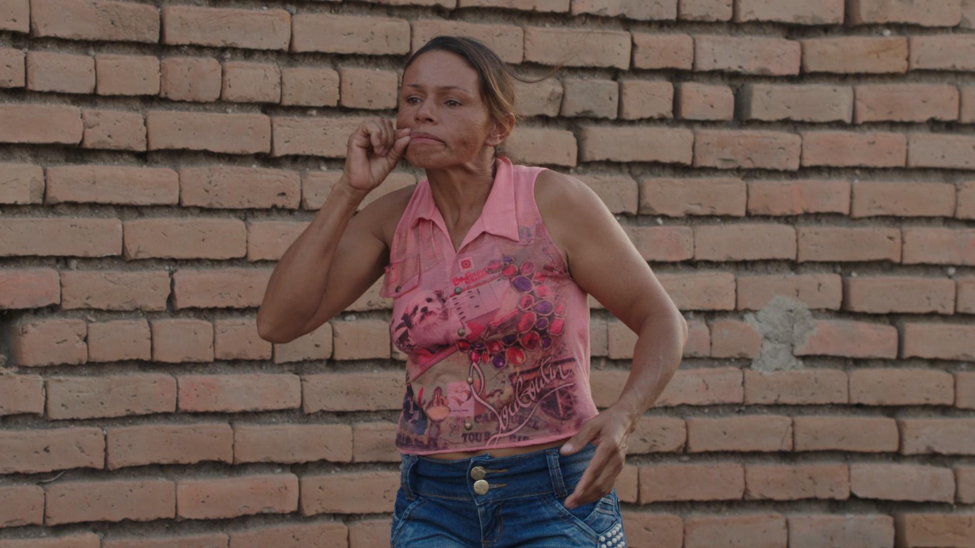 Eine Frau mit dunkler Hautfarbe und braunen, zu einem Zopf gebundenen Haaren, steht vor einer Backsteinwand. Sie trägt ein pinkes ärmelloses shirt und macht eine Gebärde.