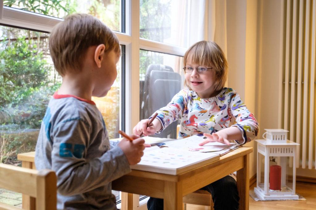zwei kinder sitzen am tisch miteinander.