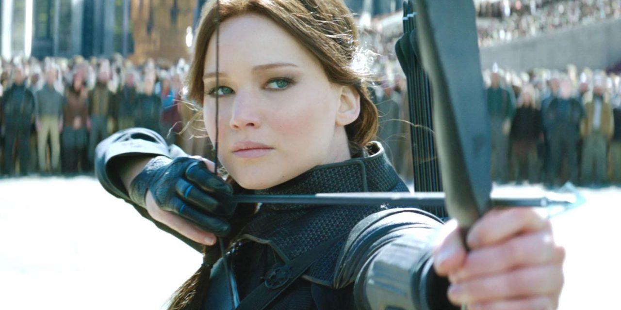 Eine Frau mit braunen Haaren ist dabei mit PFeil und Bogen zu schießen