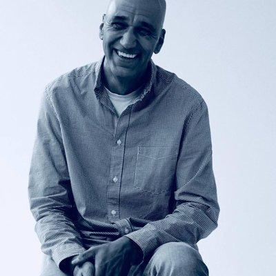 ein schwarzer mann mit glatze lächelt