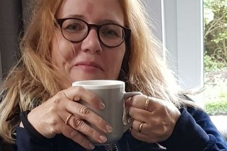 Foto von Christiane Maaß. Sie hat braune, schulterlange lockige Haare und eine runde Brille. Sie guckt in die Kamera und hält eine Tasse in der Hand.