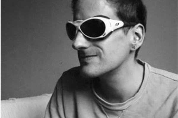 Schwarz-Weiß Foto von Heiko Kunert. Er trägt ein helles t-Shirt, hat kurze dunkle Haare und trägt eine große Sonnenbrille.