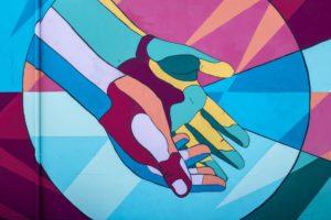 Gemälde von zwei bunten Händen die ineinander greifen.
