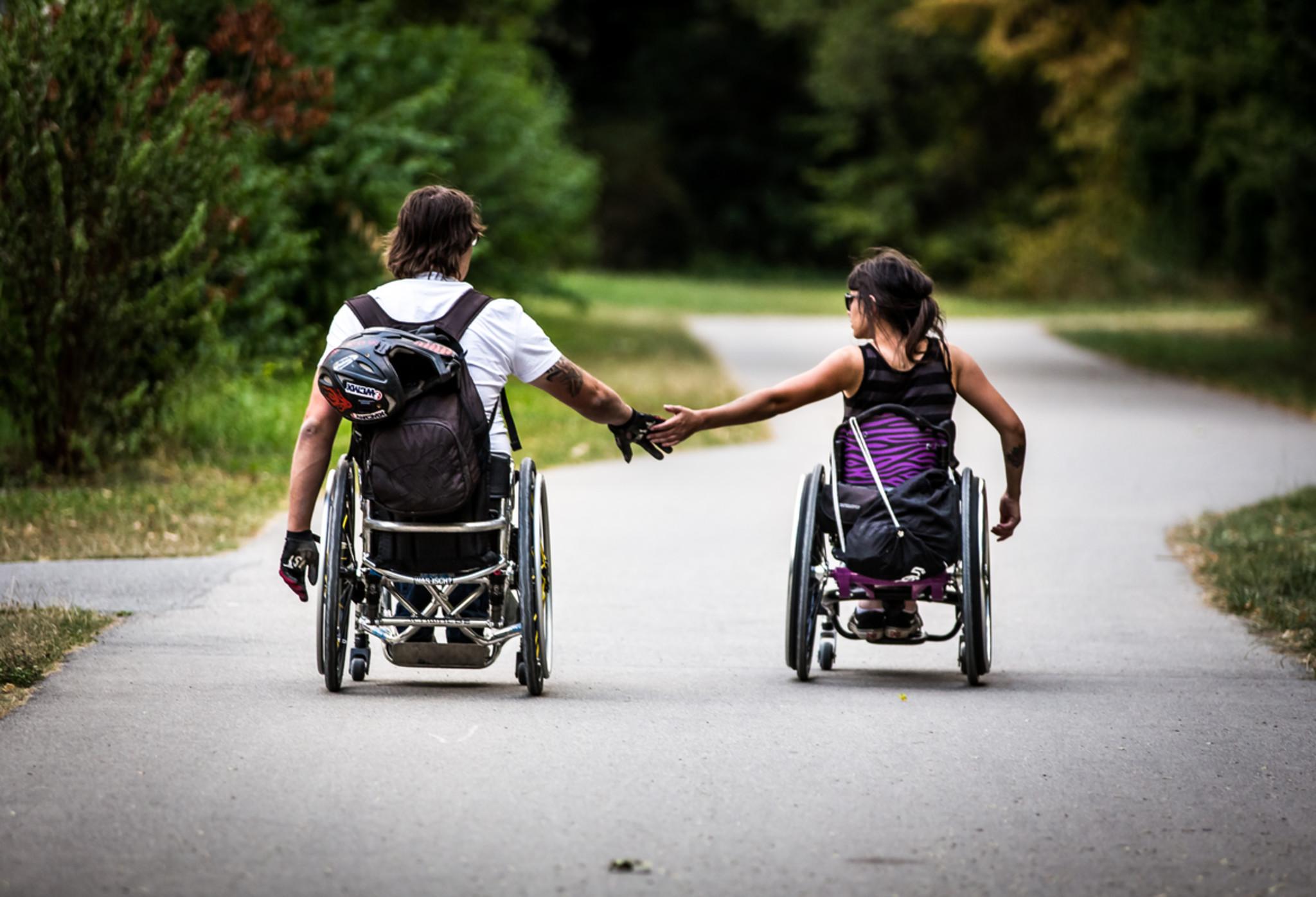 Ein Rollstuhlfahrer und eine Rollstuhlfahrerin von hinten, sie halten Händchen.
