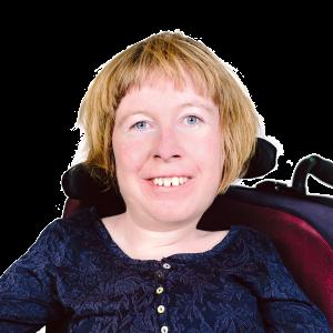Anne hat mittellange blonde Haare und sitzt im Rollstuhl. Sie lächelt in die Kamera.