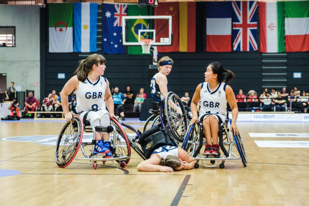 Frauen spielen Rollstuhlbasketball. Eine liegt am Boden im Rollstuhl und verzieht schmerzhaft das Gesicht.