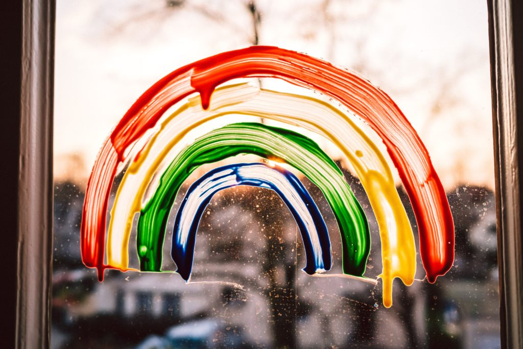 Ein Regenbogen aufgemalt auf einer Fensterscheibe