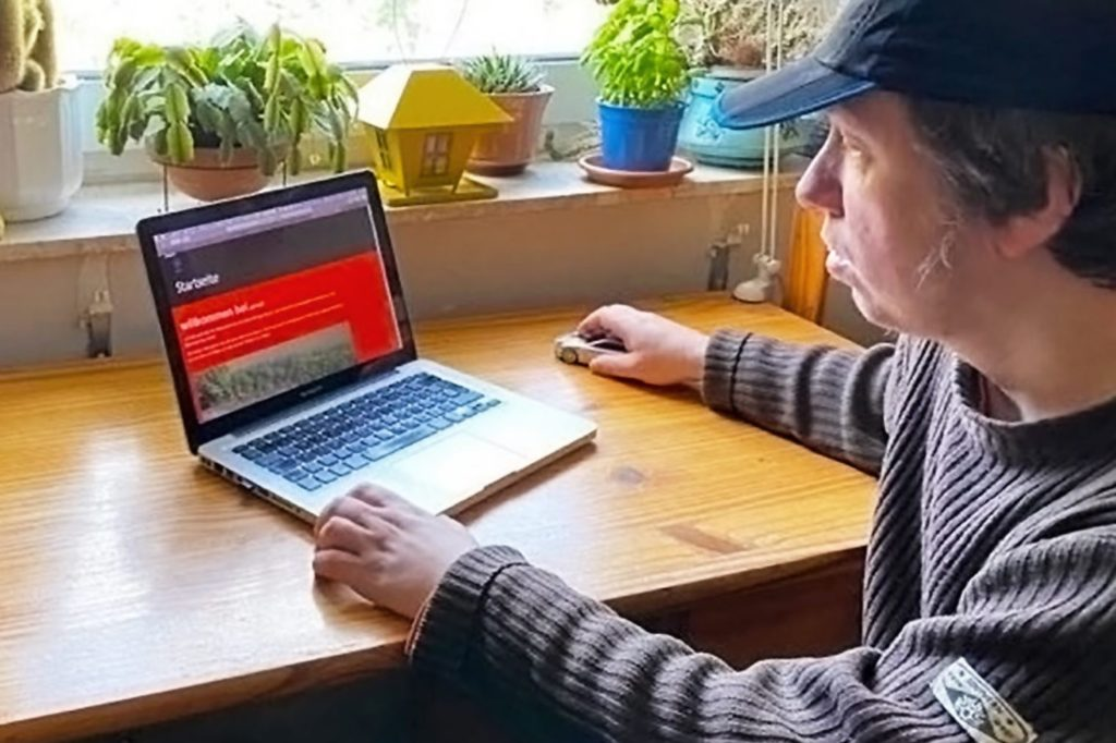 ein mann sitzt vor seinem laptop
