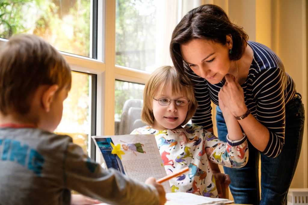 Zwei Kinder sitzen an einem Tisch und machen Hausaufgaben. Eine Frau mit langen schwarzen Haaren beut sich zu dem Mädchen mit Behinderung herunter.