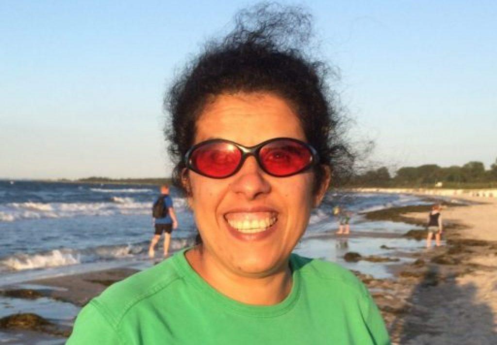 Lydia hat dunkle, vom winde verwehte, Haare. Sie trägt eine orangene Sonnenbrille und einen grünen Pullover. Sie lächelt in die Kamera.