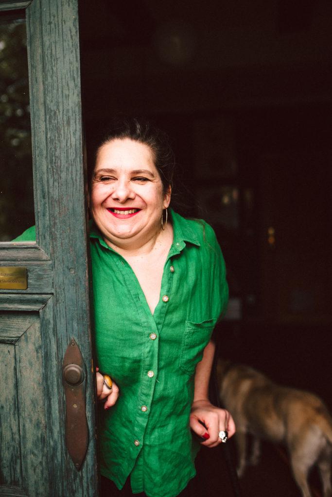 Annton Beate Schmidt trägt eine grüne Bluse und lehnt sich an eine Holztür. Sie lächelt in die Kamera.