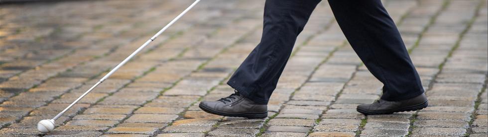 ein mensch spaziert mit langstock