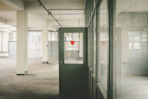 Ein leerer weißer Raum. Eine Tür mit Glasfenster steht offen, auf dem ein rotes Herz zu sehen ist.