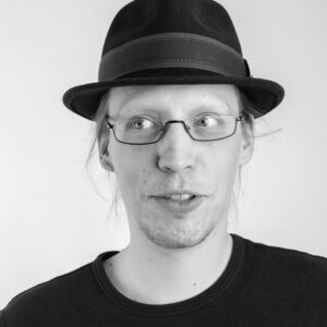 Schwarz-weiß Foto von Frederic. Er trägt eine Brille, ein schwarzes t-shirt und einen schwarzen Hut. Er schaut mit den Augen zur Seite.