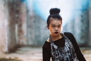 Hieu Pham trägt ein schwarz-weißes logshirt und einen dünne schwarzen Schal. Sie hat schwarze, zum Dutt hochgebundene Haare.