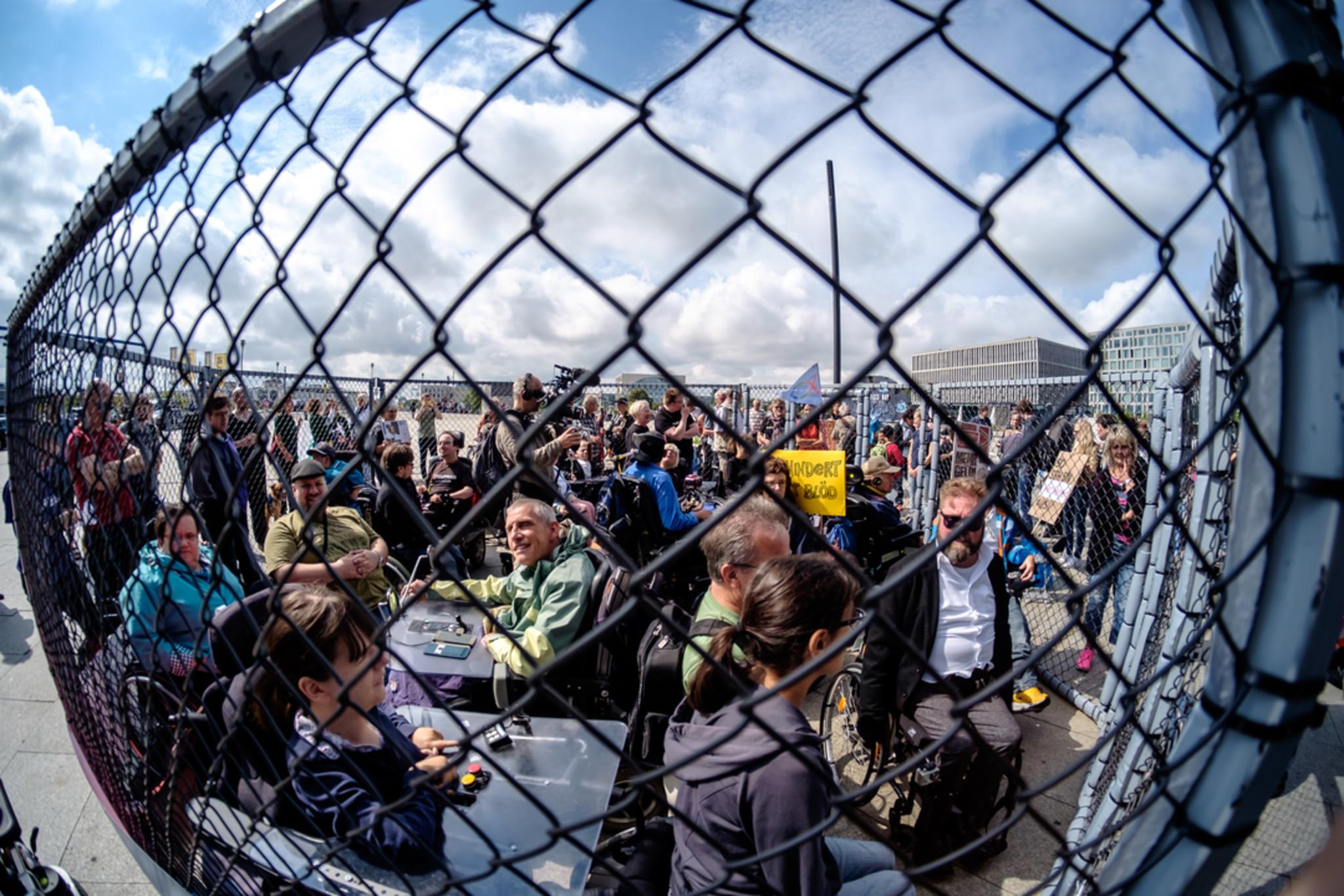 hinter einem zaun stehen behinderte und nichtbehinderte menschen dicht und demonstrieren
