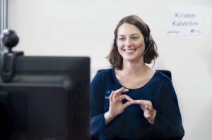 Eine Frau sitzt vor ihrem Computer und gebärdet. Sie wird dabei von ihrer Webcam gefilmt.