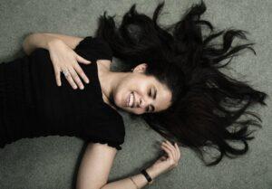 Amy liegt auf dem Rücken. Ihre schwarzen langen Haare liegen vom Kopf ab. Sie trägt ein schwarzes T-Shirt und hat die Augen geschlossen.