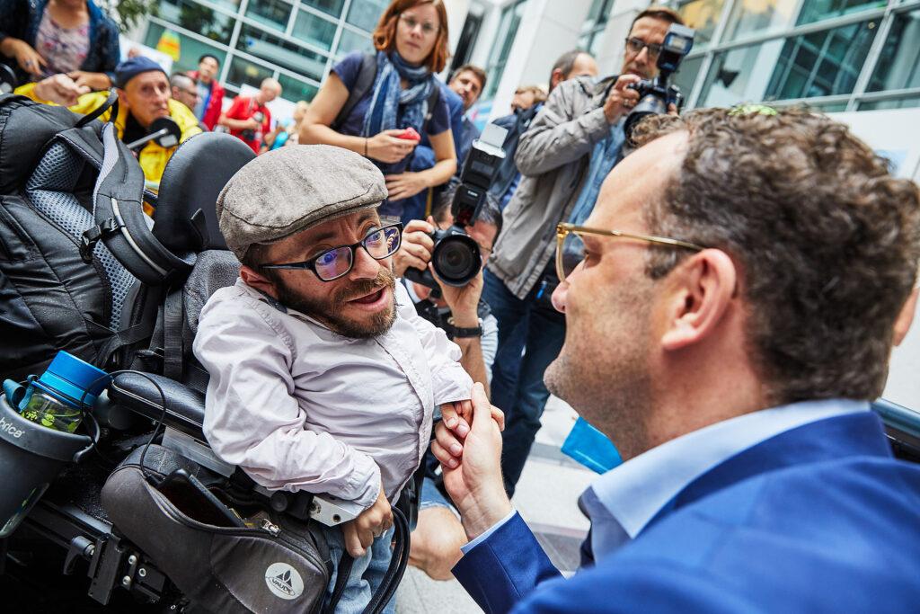 Rau Krauthausen imGespräch mit Bundesgesundheitsminister Jens Spahn. Um sie herum stehen viele demonstrierende und fotografierende Menschen.