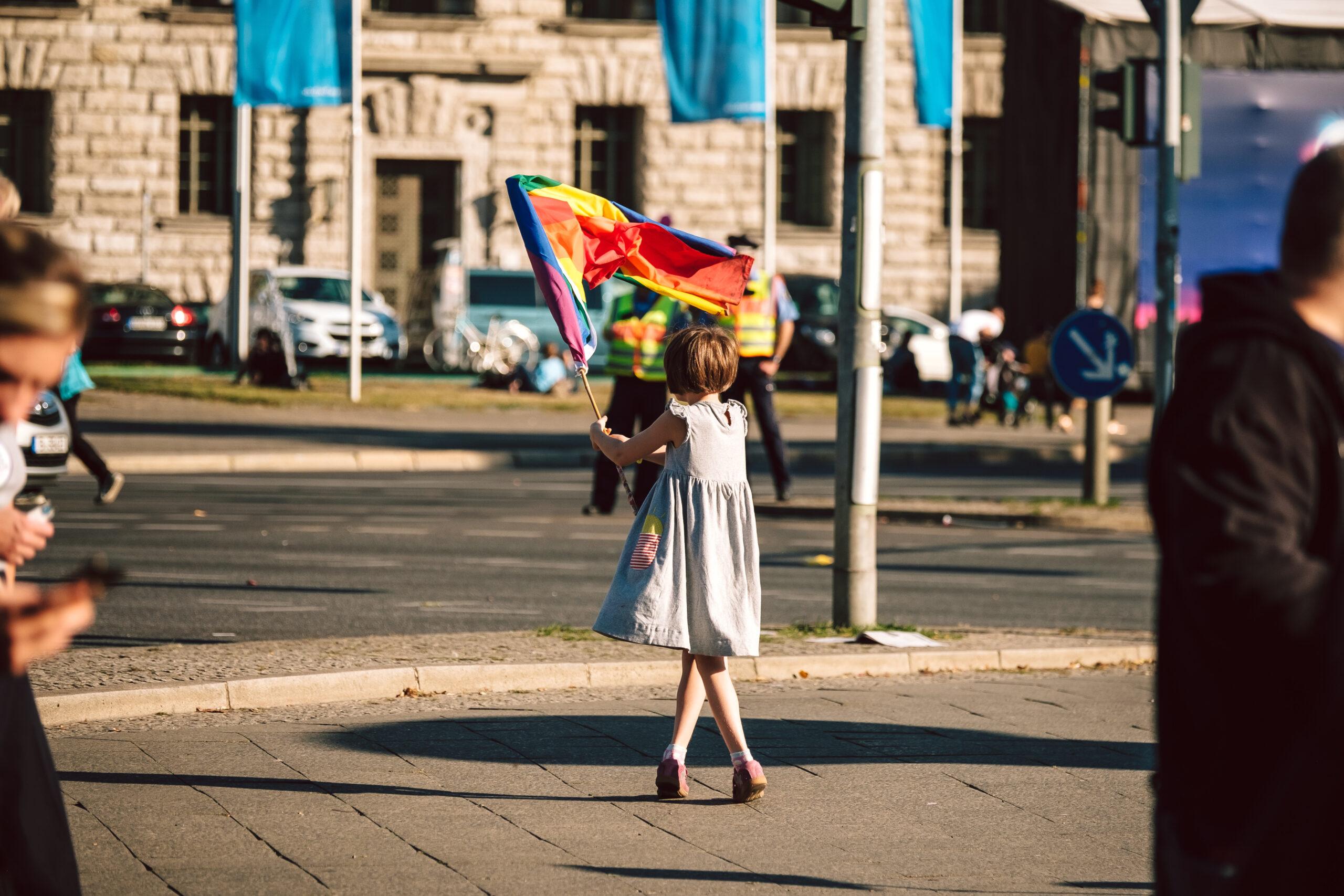 Ein junges Mädchen in einem weißen Sommerkleid ist von hinten zu sehen. Sie szeht auf der Straße und schwenkt eine bunte Fahne.
