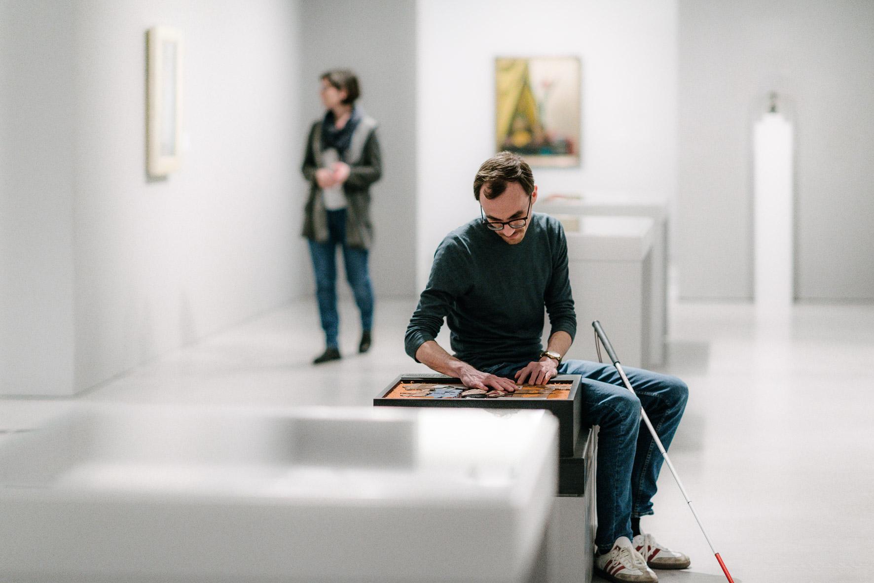 Andreas sitzt in einem weißen Ausstellungsraum und tastet mit seinen Händen einen kunstgegenstand ab.