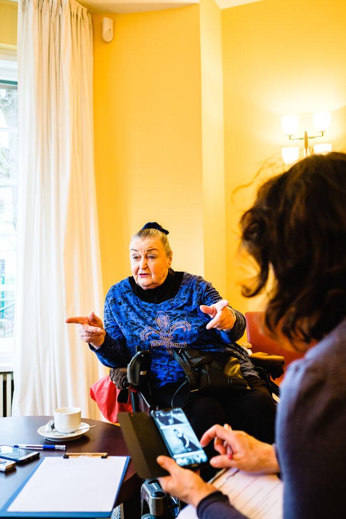 Eine Frau sitzt in einem Raum,. Im vordergrund ist der Fotograf zu sehen, der Bilder auf einem Display kontrolliert.