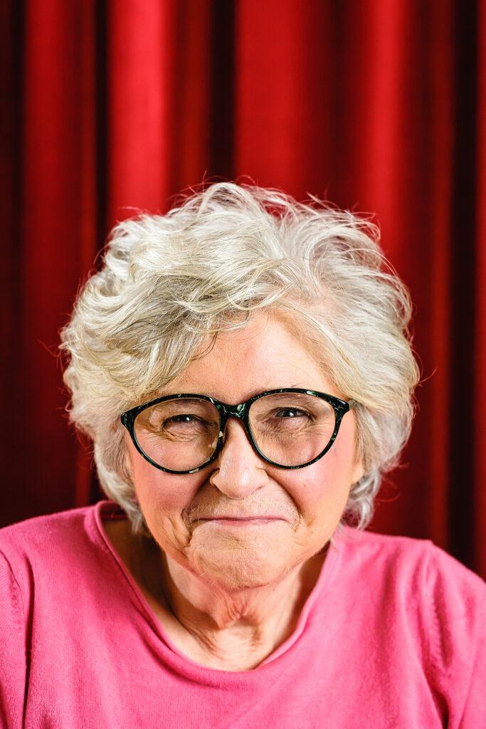 Eine ältere Frau mit weißen, lockigen Haare, schwarzer Brille und rosa Bluse steht vor einem roten Vorhang und lächelt in die Kamera.