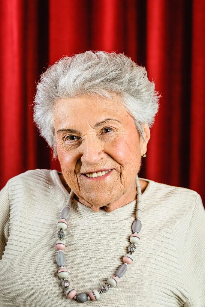 Eine ältere Frau mit grauen kurzen Haaren trägt einen beigen Pullover und lächelt in die Kamera. Sie sitzt vor einem roten Vorhang.