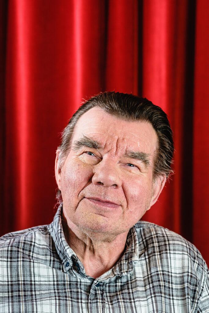 Ein älterer Mann mit schwarz-grauem kurzen Haar sitzt vor einem roten Vorhang.