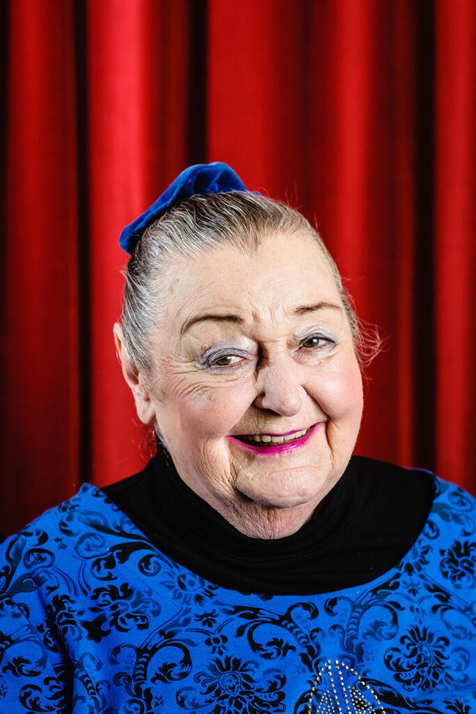 Eine ältere Frau mit blau-schwarzer Bluse und hochgebundenen Haaren steht vor einem roten Vorhang.