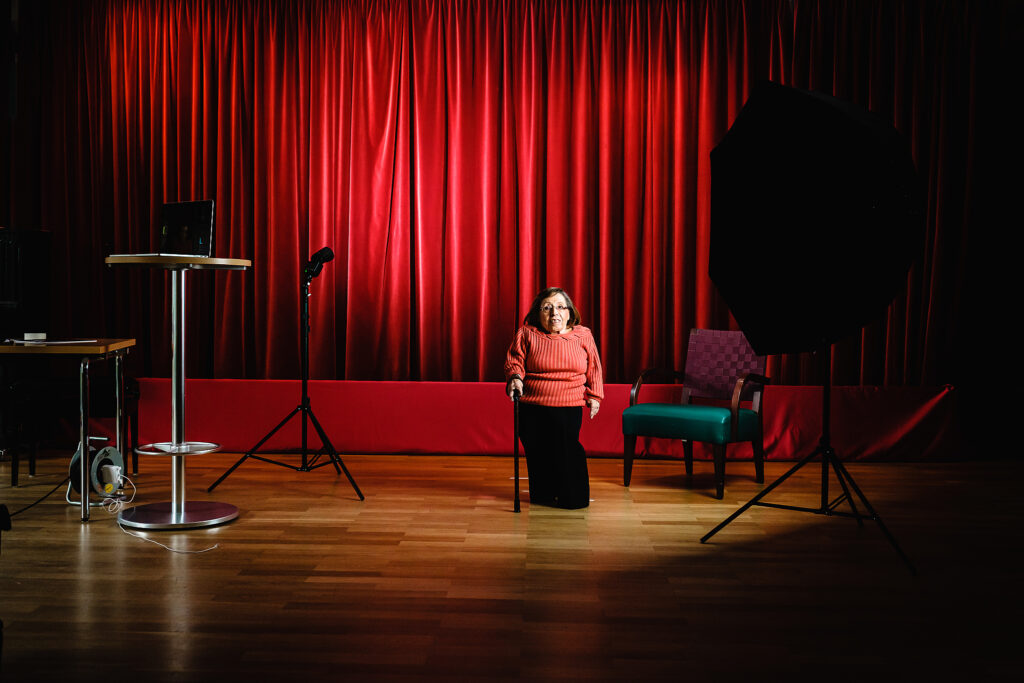 Eine kleinwüchsige, ältere Frau mit einem Stock in der Hand, sthet in einem Theater entfernt vor einem roten Vorhang.