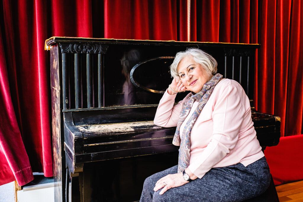 Eine ältere Frau mit weißen Haaren sitzt vor einem schwarzen Klavier und stützt ihren Kopf darauf ab.