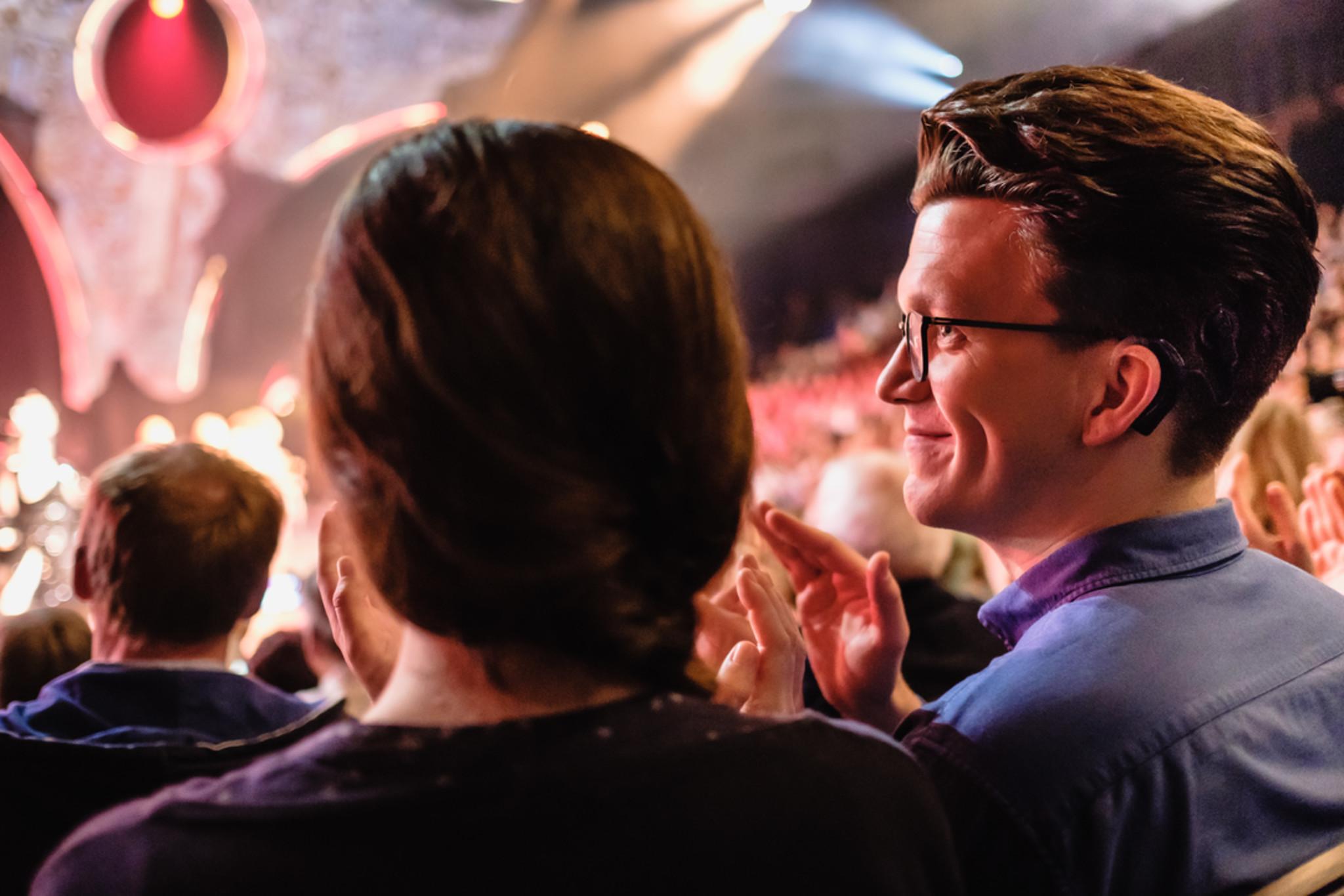Wille ist von der Seite zu sehen, wie er neben einer anderen Person im Publikum eier Veranstaltung steht.