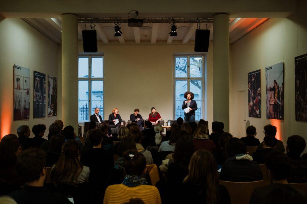 In einem dunkeln Raum sitzen vier Personen auf einem Podium. Rechts daneben steht eine Moderatorin mit einem mikrofon in der Hand.