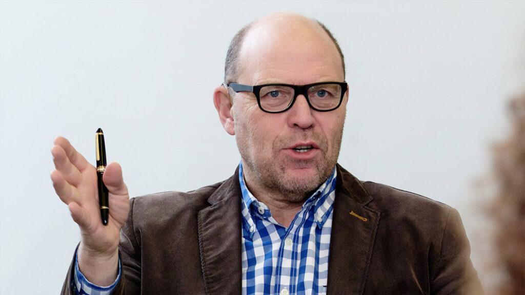 Foto von Ulrich Hase. Er hat eine Halbglatze, trägt eine Brille, ein blau-weiß kariertes Hemd und ein schwarz-brunes Sakko.