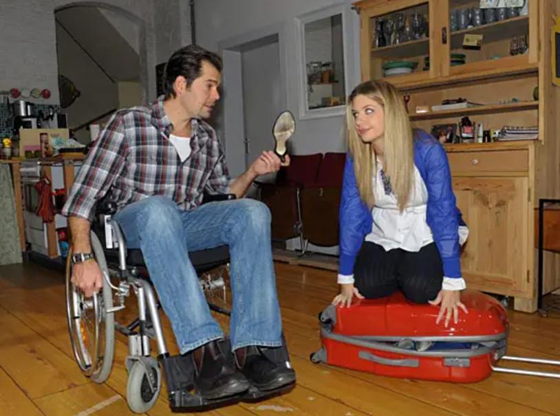 Ein Mann sitzt im Rollstuhl. Neben ihm kniet eine Frau auf einem Rollkoffer.