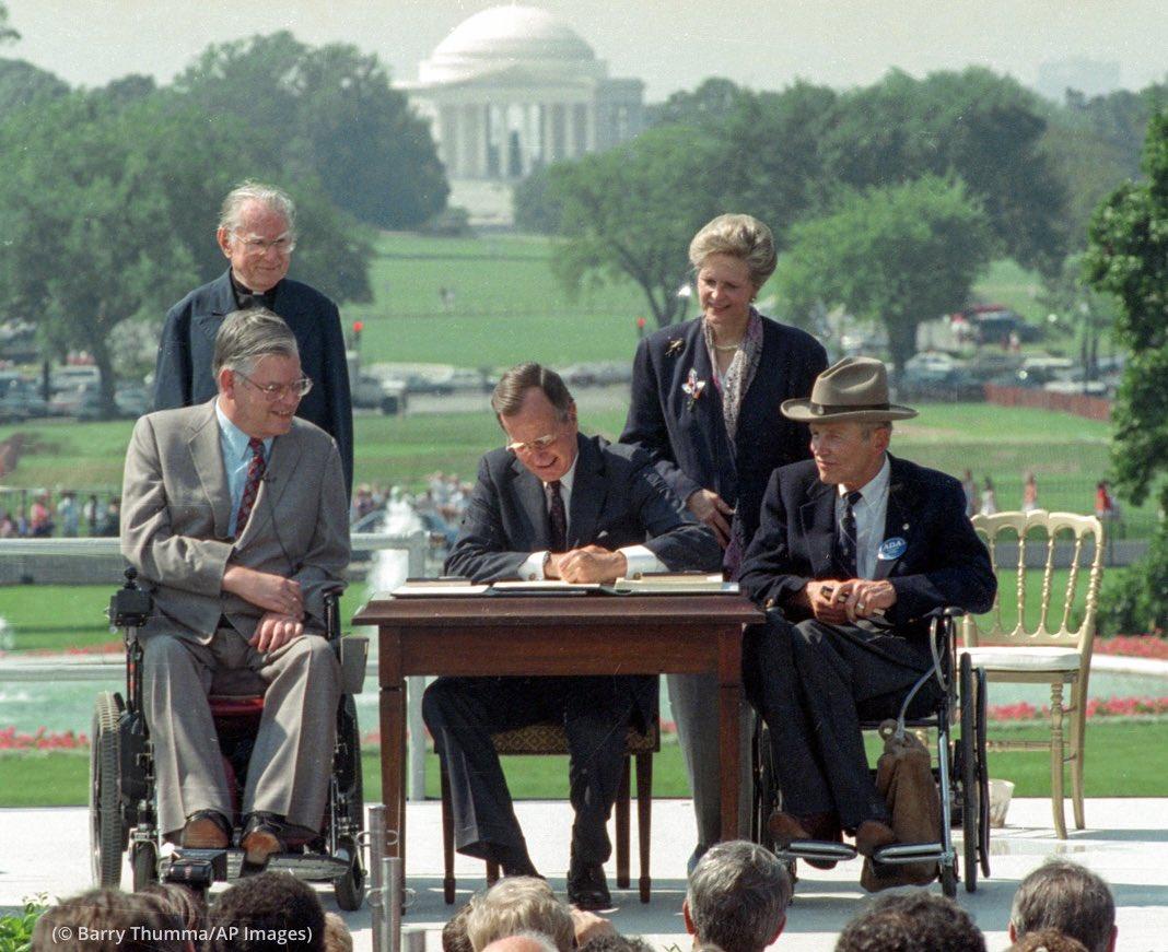 Im Garten des weißen Hauses in Washington sitzt George H.W. Bush an einem Tisch und unterschreibt den Americans with Disabilities Act (ADA). Neben ihm sitzen zwei Personen im Rollstuhl. dahinter stehen zwei weitere Personen.