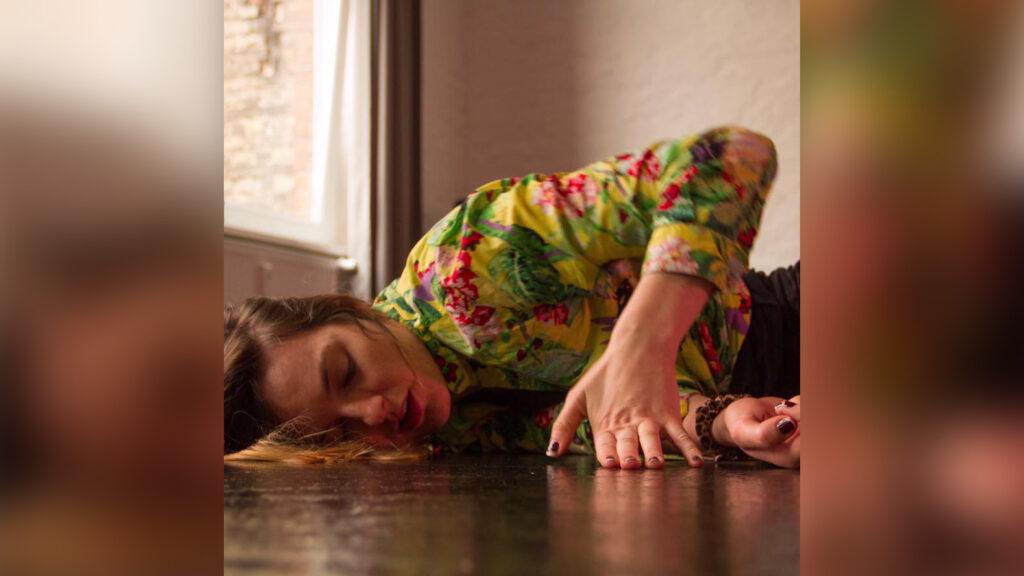 Carolin trägt eine bunte, geblümte Bluse, hat lange braune, lockige Haare und liegt mit ihrem Körper auf dem Boden.