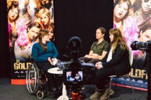 """Judyta Smykowski sitzt im Rollstohl an einem kleinen Tisch. Ihr gegenüber sitzen die beiden Schauspieler*innen Tom Schilling und Luisa Wöllisch. Hinter ihnen sind Plakate des Kinofilms """"Die Goldfische"""" aufgehangen. Vor ihnen steht eine Kamera, die das Gespräch filmt."""