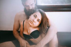 Eine Frau mit schwarzer Unterwäsche wird von hinten von einem ebenfalls leicht bekleideten Mann umarmt. Sie hat schulterlange dunkelbraune Haare und trägt ein Beatmungsgerät. Sie schaut in die Kamera.