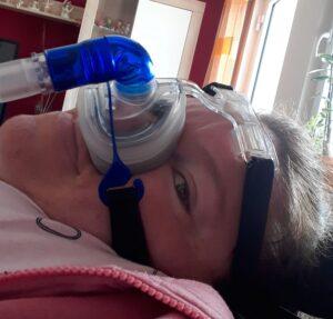 Eine Frau liegt in ihrer Wohnung an einem Beatmungsgerät.