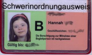 """Ein Schwerbehindertenausweiß zeigt eine junge Frau mit Down-Syndrom. Der Titel """"Schwerbehindertenausweis ist mit einem weißen Zettel überklebt, auf dem """"Schwer in ordnung Ausweis"""" steht."""