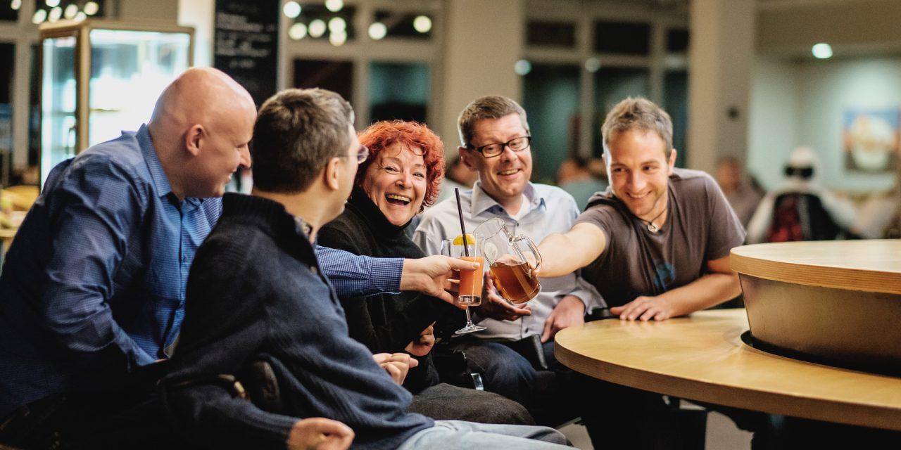 Eine Gruppe von Menschen mit Behinderungen sitzt an einem Tisch und stößt mit Getränken an.